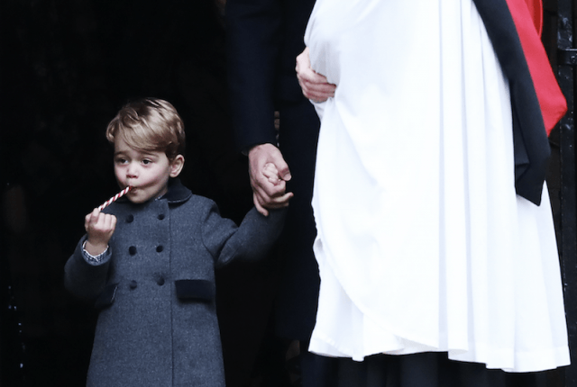 Prince George eating a candy cane while holding his father's hand.