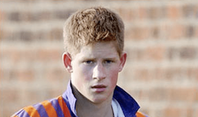 A young Prince Harry stands in front of a brick wall.
