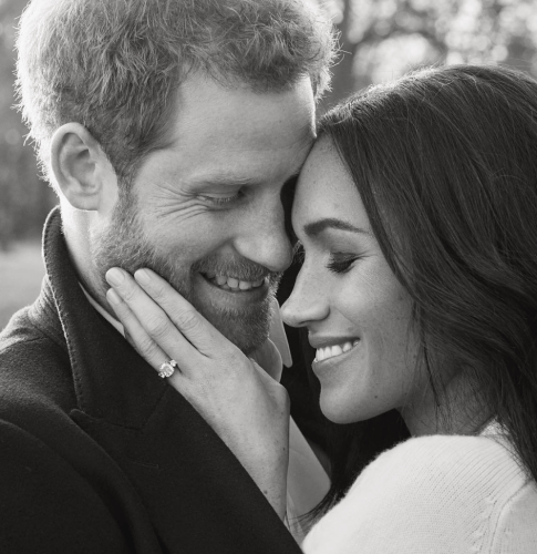 Prince Harry and Meghan Markle smiling while they embrace.
