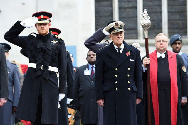 Prince Harry saluting while standing next to Prince Phillip.