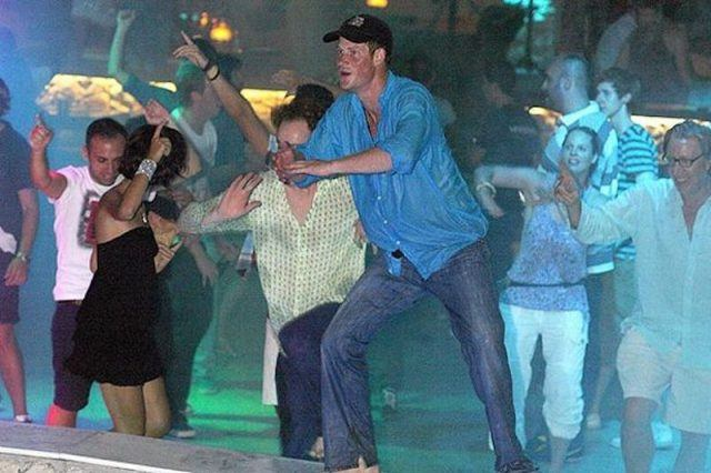 Prince Harry dancing in a pool with other party goers.