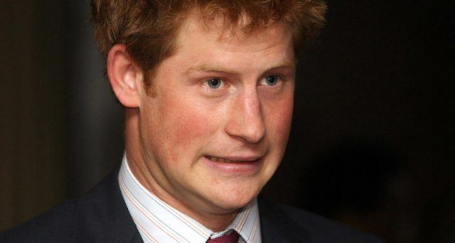 Prince Harry grimaces while wearing a black suit.