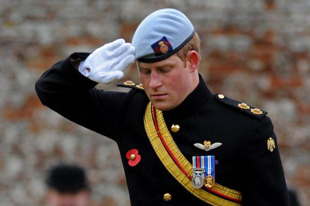 Britain's Prince Harry, salutes after laying a cross of remembrance in memory of his friend Lance Corporal