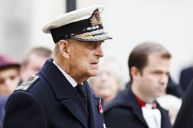 Prince Phillip walking straight forward while dressed in a naval uniform.