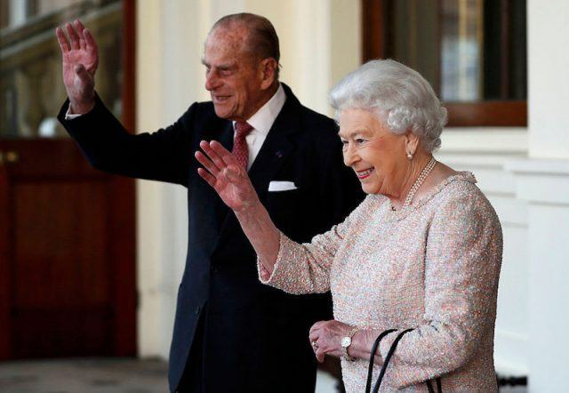 Prince Phillip waves while standing next to Queen Elizabeth.