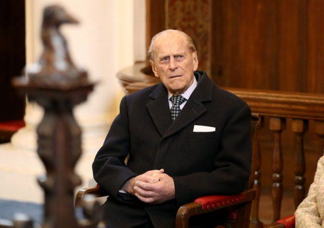 Prince Phillip sitting in a chair while wearing a black jacket and tie.
