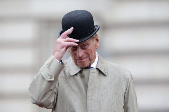 Prince Phillip holds his hat while standing in the rain.