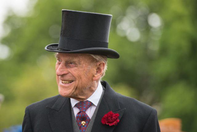 Prince Charles wearing a tall hat and a suit and tie.