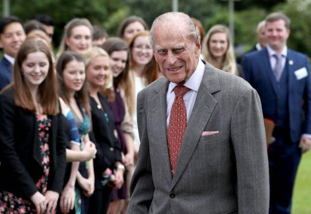 Prince Phillip smiles while standing in front of a group of onlookers.