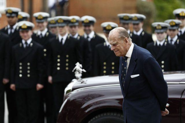Prince Phillip stands in front of a naval army and shiny car.