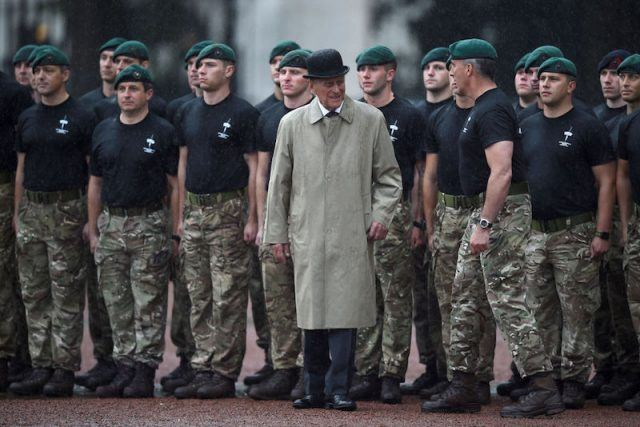 Prince Phillip stands in front of a group of young soldiers.