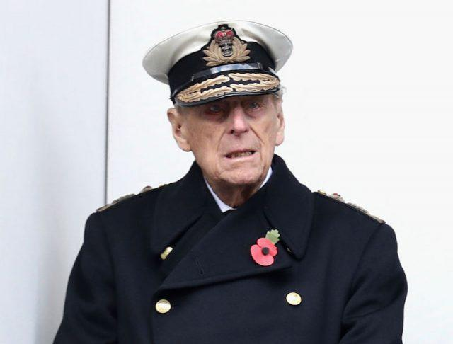 Prince Phillip stands while wearing a uniform.