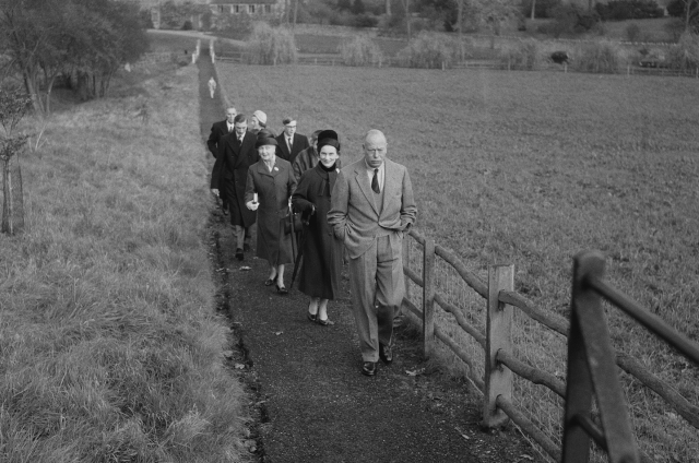 Princess Anne walking alongside a farm with a group of family members and friends.