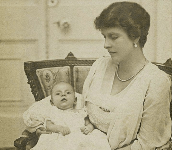 Princess Alice holding her baby while wearing a suit and jewelry.