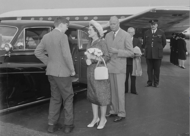 Princess Alice in front of a plane and car.