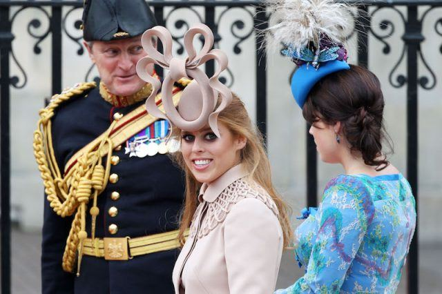 Princess Beatrice smiles while wearing a dress and hat.