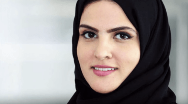 Princess Sheikha smiles in front of a white background.