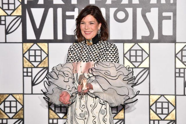 Princess Caroline of Hanover stands in a gown in front of a patterned wall.