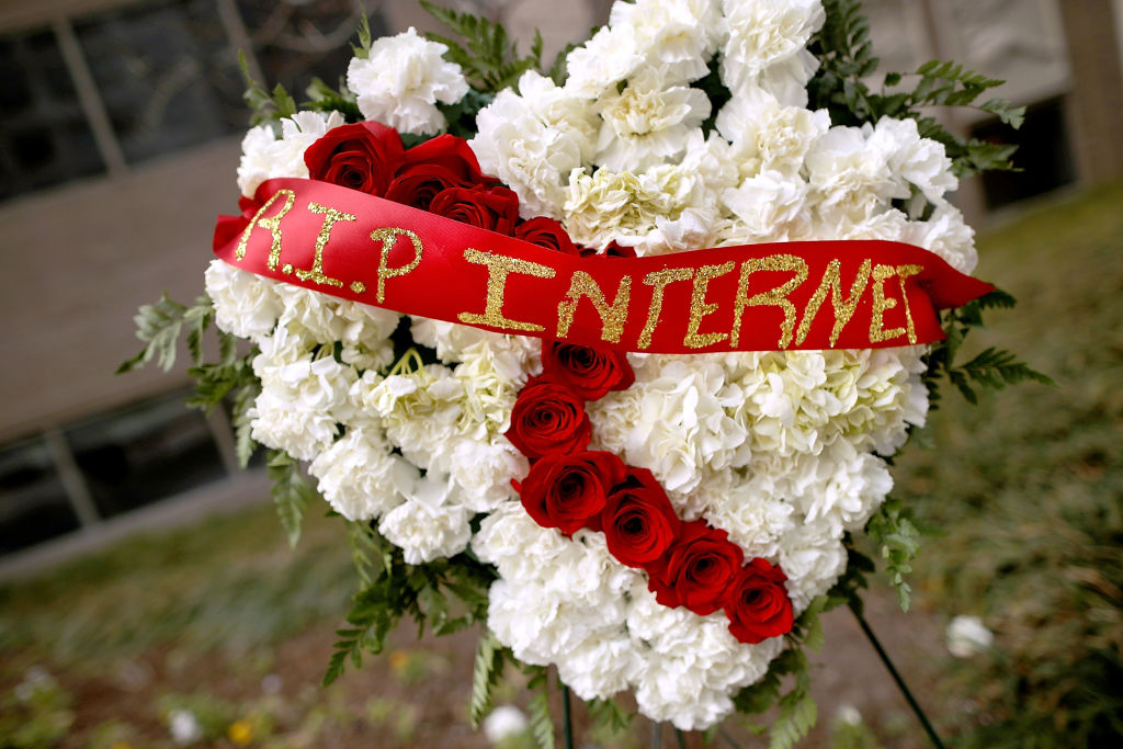 A funeral flower arrangement is set up outside the Federal Communication Commission building