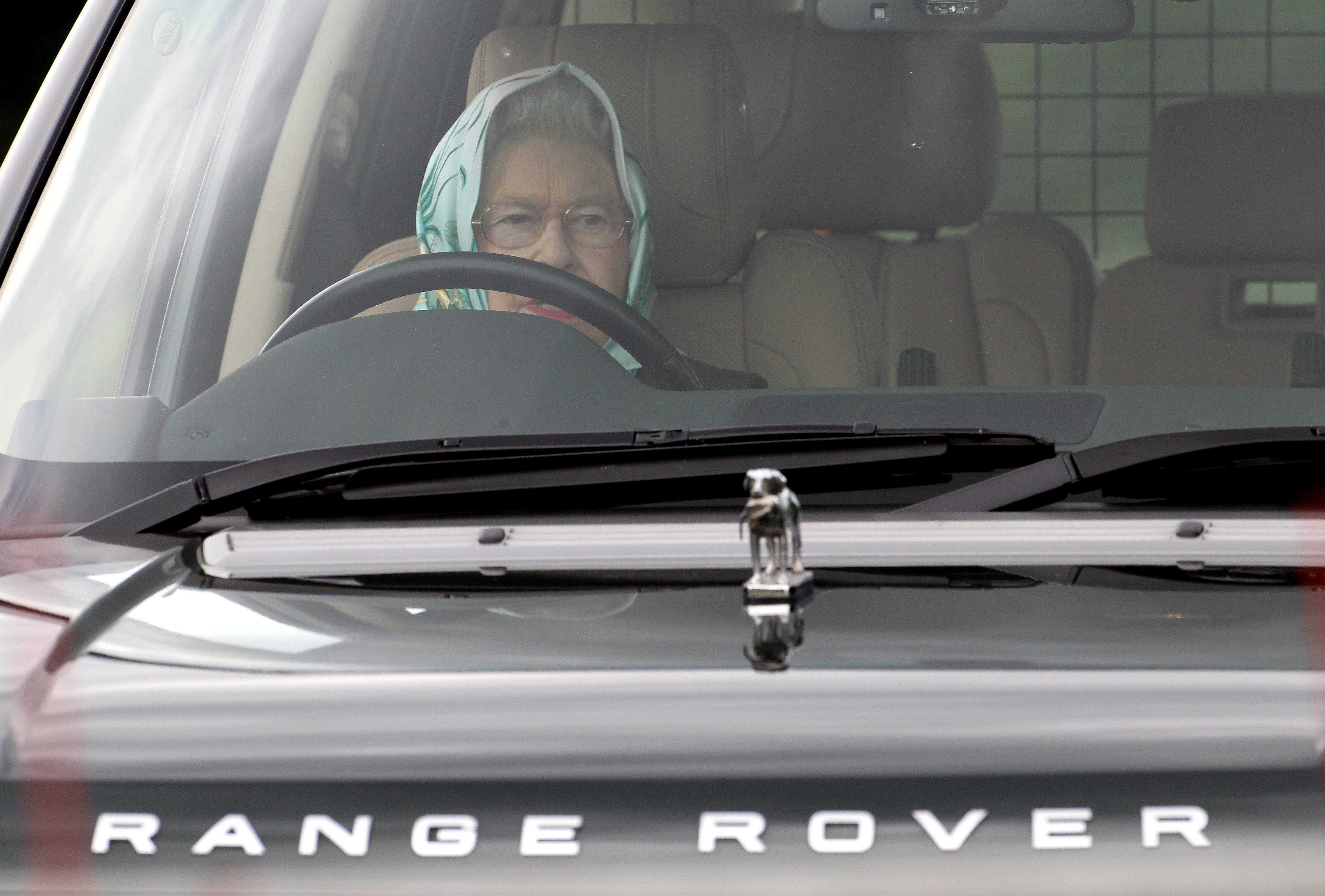Queen Elizabeth drives a car with her hair in a scarf