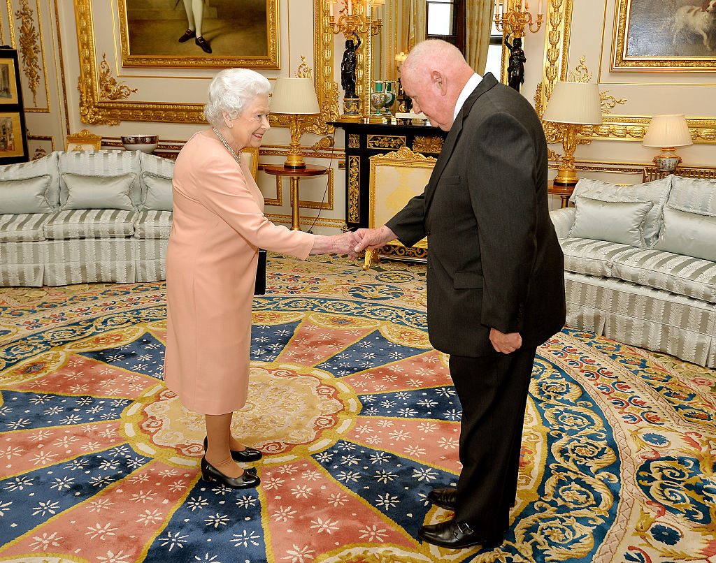 Queen Elizabeth II shakes hands with American businessman John Mars