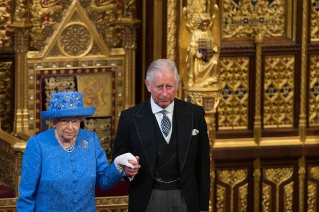 Queen Elizabeth and Prince Charles stand together holding hands.