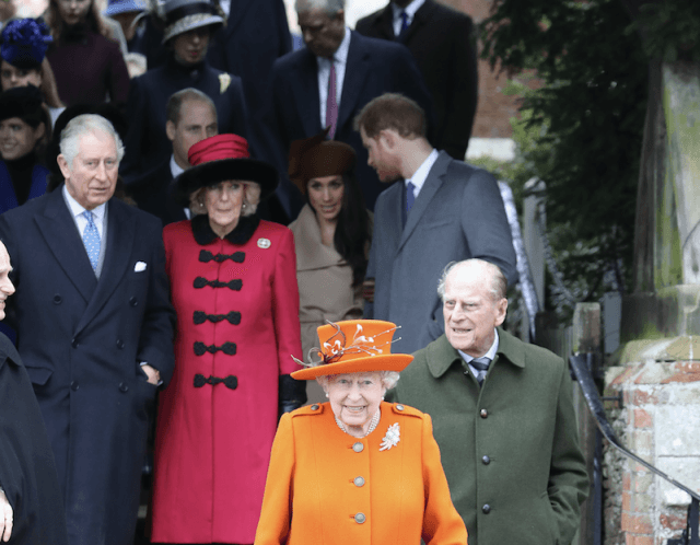 Queen Elizabeth stands in front of Prince Phillip.