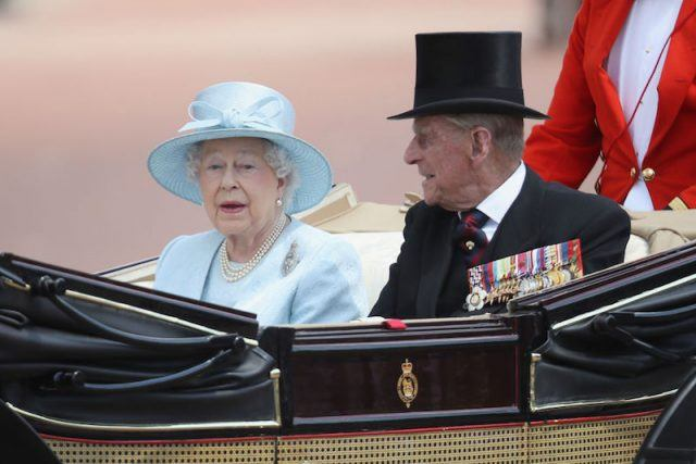 Queen Elizabeth and Prince Phillip riding in a coach.