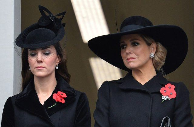 Kate Middleton and Queen Maximum stand together wearing black clothes.