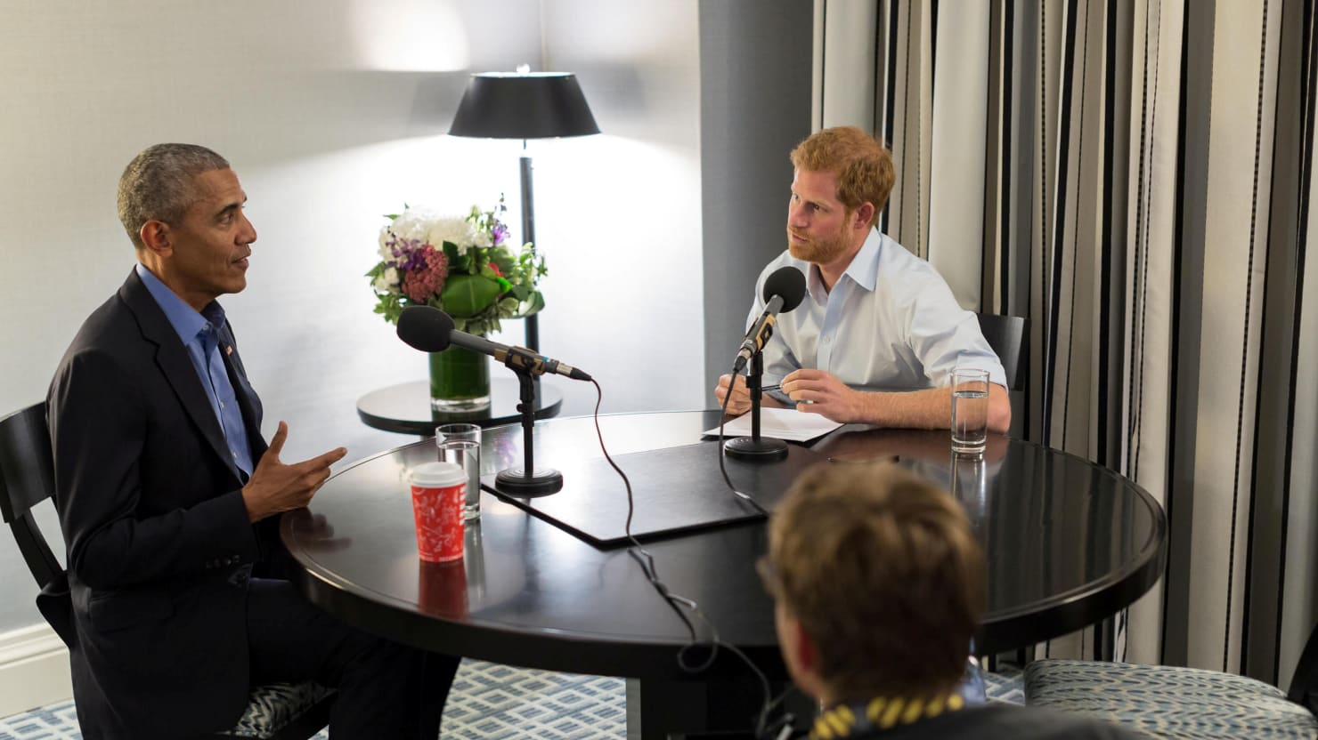 Prince Harry and Barack Obama sit at a round table in front of microphones