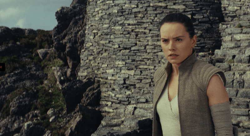 Rey stands in front of a brick wall
