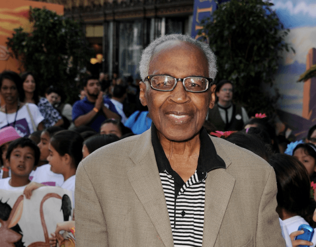 Robert Guillaume posing in a tan jacket and glasses.