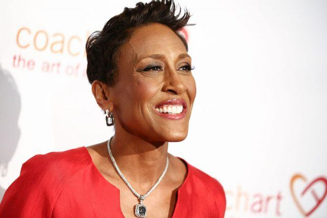 Robin Roberts smiling while wearing a red dress and jewelry at a gala in Beverly Hills.
