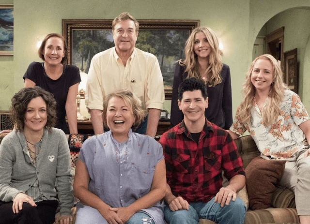 The cast of Roseanne sitting and smiling on their couch set.