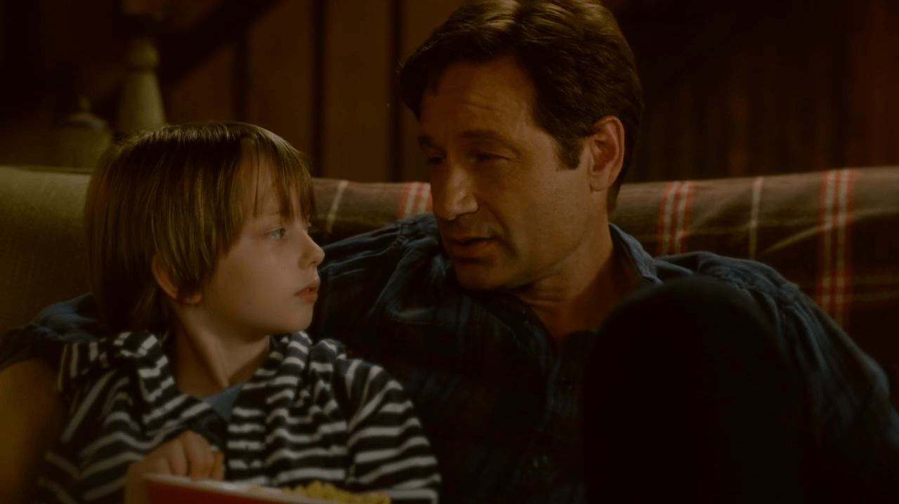 Mulder sits on a couch with his arm around a young boy