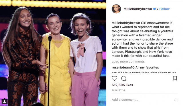 A photo of Millie Bobby Brown standing in front of microphone with two other girls