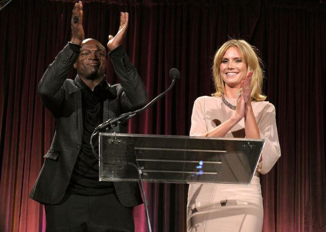 Seal and Heidi Klum applauding while making a speech at a podium.