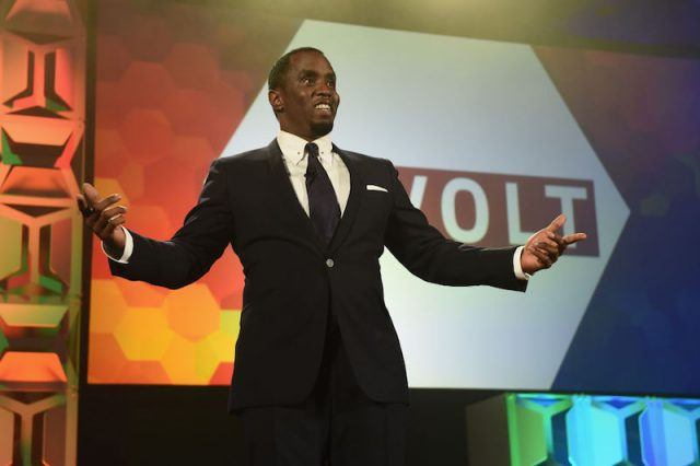 Sean Combs addresses an audience in a black suit.