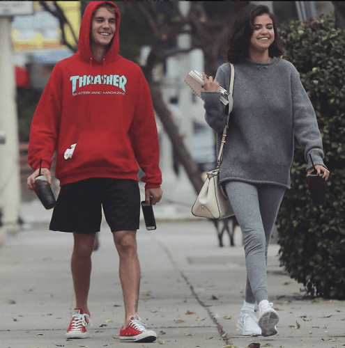 Selena Gomez and Justin Bieber walk together while drinking coffee.