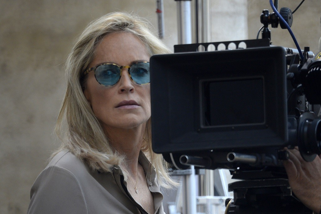 Between takes, Sharon Stone stands on set.