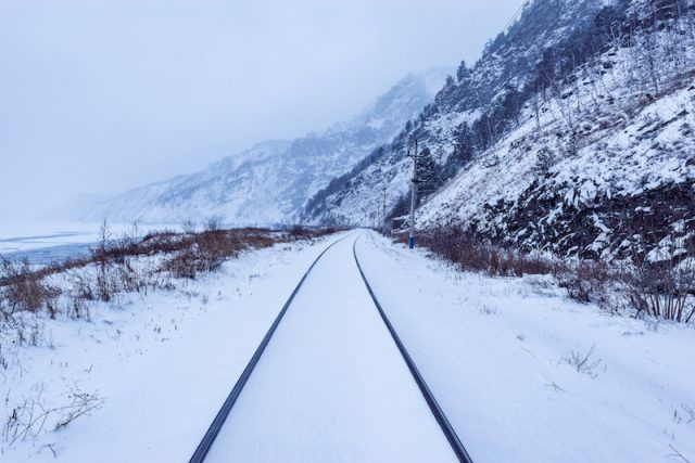 Snow covered tracks and mountains.