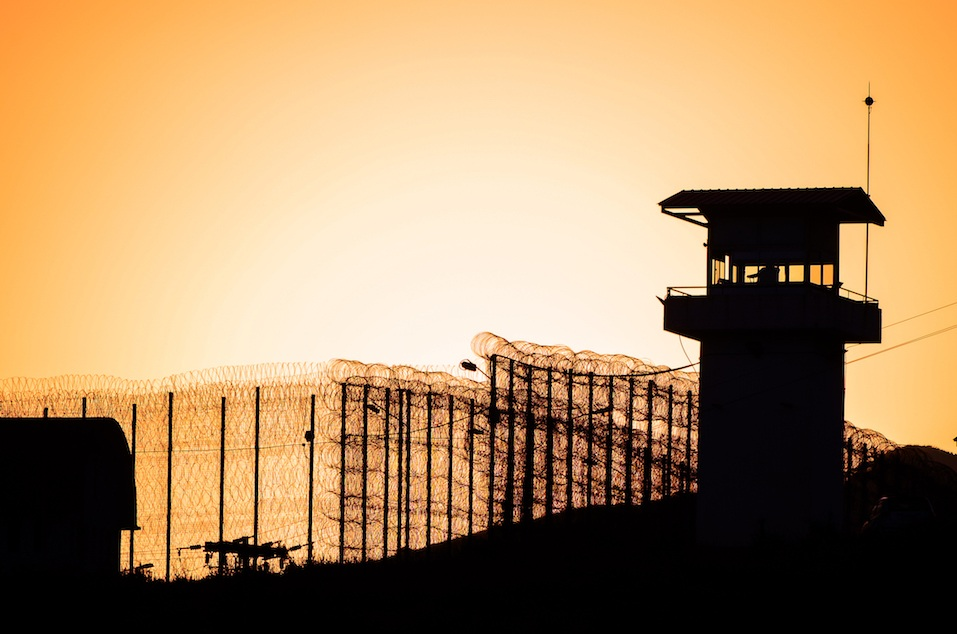 Silhouette of barbed wires and watchtower of prison.