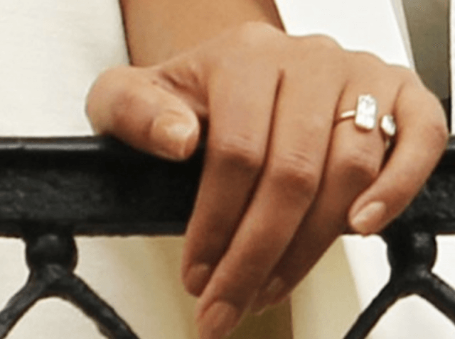Solange Knowles' diamond engagement ring on her hand as she leans over a balcony rail.
