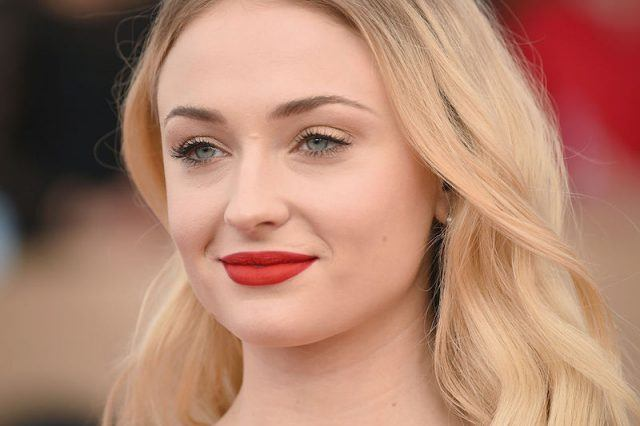 Sophie Turner smiling while wearing a bold red lipstick.