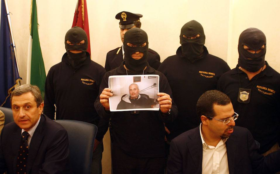 Special squad police officers show a picture of Mafia boss Domenico Raccuglia after he was brought by police following his arrest to the police headquarters in Palermo