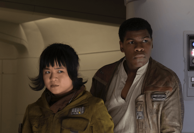 Rose and Finn stand close together and focus on something in front of them.