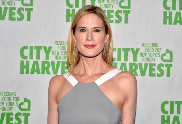 Stephanie March posing in a gray and white dress at a charity event.