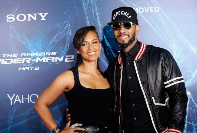 Swizz Beatz and Alicia Keys posing in front of a blue wall.
