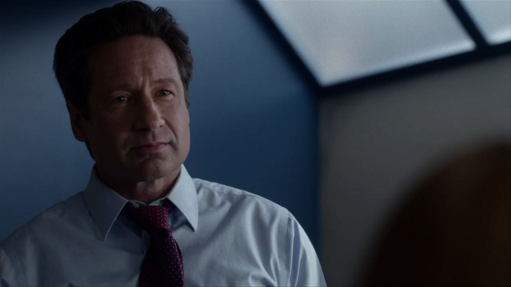 Mulder stands and looks ahead in a blue shirt with red tie