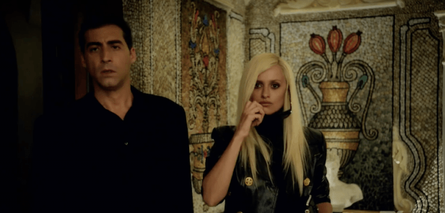 Donatella Versace removing her sunglasses while standing next to a man.
